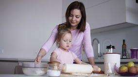 Kaukaska młoda kochająca matka joyfully pomaga jej ślicznej małej córki tocznej za cieście z toczną szpilką podczas gdy zbiory