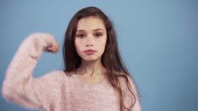 Kaukaska nastoletnia dziewczyna utrzymuje sekret lub pyta dla ciszy przeciw błękitnemu tłu, zapina jej usta poważną twarz zbiory