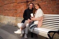 Kaukaska para w miłości w parkowym obsiadaniu na ławce blisko ściany z cegieł z takeaway napojem fotografia royalty free