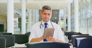 Kaukaska samiec lekarka trzyma cyfrową pastylkę w lobby przy biurem 4k zbiory