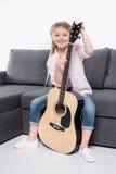 Kaukaska uśmiechnięta dziewczyna siedzi na kanapie i trzyma gitarę w przypadkowych ubraniach obraz stock