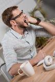 Kaukaski biznesmen gryźć pięść i obsiadanie przy workspace w eyeglasses Obrazy Royalty Free