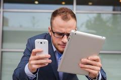 Kaukaski biznesmen na zewnątrz biurowego używa telefonu komórkowego i tabl Obraz Stock
