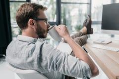 Kaukaski biznesmen pije kawę podczas gdy siedzący przy workspace Zdjęcia Stock