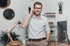 Kaukaski biznesmen używa smartphone i opierający na stole przy workspace Obrazy Stock