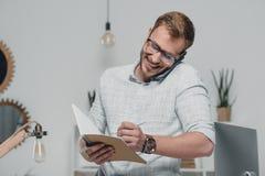 Kaukaski biznesmen używa smartphone i pisać w dzienniczku w nowożytnym biurze Zdjęcia Stock