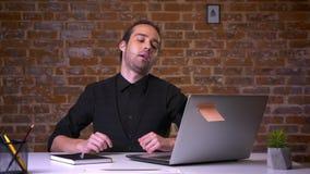 Kaukaski biznesmena obsiadanie z rękami za głową w ceglanym biurze relaksował za komputerem