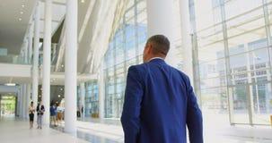 Kaukaski biznesmena odprowadzenie w lobby przy biurem 4k zbiory