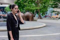 Kaukaski Biznesowej kobiety stojak i opowiadać na telefonie komórkowym Fotografia Stock