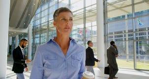Kaukaski bizneswomanu odprowadzenie w lobby przy biurem 4k zbiory
