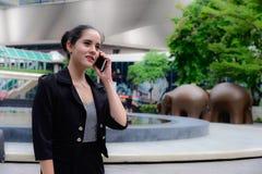 Kaukaski bizneswomanu stojak i opowiadać na telefonie komórkowym Fotografia Stock