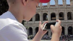 Kaukaski chłopiec turysta texting na pięknym widoku europejski antyczny miasto z mobilnym mądrze telefonem zbiory