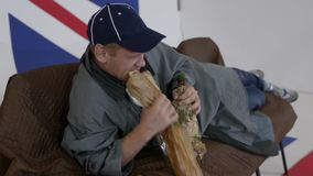 Kaukaski dorośleć mężczyzna w nakrętce i żakiet kłama na kanapie, je bochenek chleb i pije, zbiory