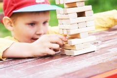 Kaukaski dzieciak bawić się drewnianych bloków basztową grę dla ćwiczyć fizyczną i umysłową umiejętność zdjęcia royalty free