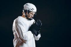 Kaukaski gracz w hokeja w mundurze, odizolowywającym na czerni, modli się na dobre szczęście fotografia royalty free