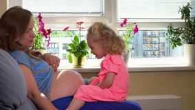 Kaukaski kobieta w ciąży i śliczna blond córki dziewczyna bawić się z brzuchem w domu zdjęcie wideo
