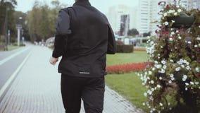 Kaukaski mężczyzna bieg wzdłuż ruchliwie miasto ulicy swobodny ruch Boczny widok Zdecydowany mężczyzna pracujący w miastowych oto zdjęcie wideo
