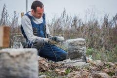 Kaukaski mężczyzna budowniczy pracuje z kurendą zobaczył outdoors wokoło, trocinowy latanie zdjęcie stock
