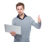 Kaukaski mężczyzna chwyt z laptopem up i kciukiem Obrazy Stock