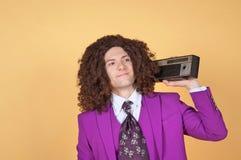 Kaukaski mężczyzna jest ubranym purpury z afro Nadaje się słuchanie muzyka Obraz Royalty Free