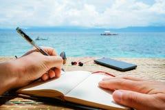 Kaukaski mężczyzna pisze pomysle, wiadomości lub liście sime, w jego notepad piórem podczas gdy on siedzi na plaży tropikalny Obrazy Royalty Free