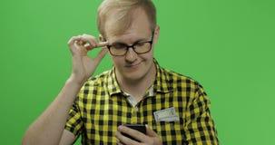 Kaukaski mężczyzna w szkłach scrolling ręki lub texting na smartphone w jego zdjęcie wideo