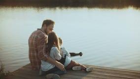 Kaukaski mężczyzna z dwa dziećmi ogląda wodnych ptaki Szczęśliwy tata i dzieciaki siedzimy wpólnie na zmierzchu jeziora molu Dzie zdjęcie wideo