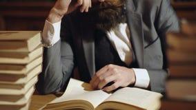 Kaukaski męski czytanie, kręcenie wiązka książka w stole, książka wzywa Brodatego mężczyzny czytelnicza książka na drewnianym sto zbiory wideo