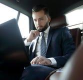 Kaukaski męski dyrektora wykonawczego podróżowanie samochodem i działanie na laptopie Zdjęcia Royalty Free