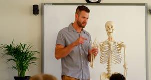 Kaukaski męski nauczyciel wyjaśnia kośca modela w sali lekcyjnej przy szkołą 4k zbiory wideo
