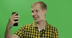 Kaukaski młody człowiek w żółtej koszula bierze śmiesznych selfies na smartphone zdjęcia royalty free