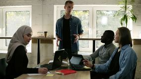 Kaukaski młody człowiek w przypadkowym daje wyjaśnieniu projekt jego partnery lub colleguaes Różnorodna multiracial drużyna zbiory wideo