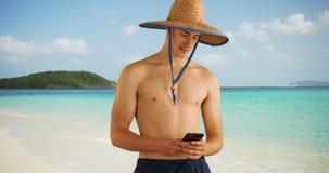 Kaukaski męski texting na telefonie komórkowym od Karaibskiego brzeg Fotografia Stock