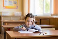 Kaukaski ma?y u?miechni?ty dziewczyny obsiadanie przy biurkiem w klasowym pokoju i zaczyna rysowa? w czystym notatniku zdjęcie royalty free