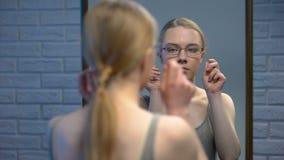 Kaukaski nastolatka odmawianie by? ubranym eyeglasses, z przykro?ci? patrzeje lustrzanego odbicie zbiory wideo