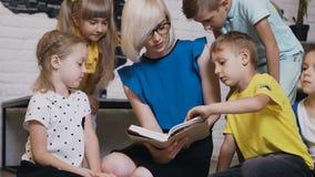 Kaukaski nauczyciel i jej ucznie siedzimy na małe poduszki czytamy książkę w sala lekcyjnej w szkole podstawowej wpólnie lub zbiory