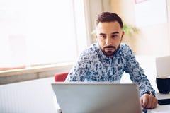 Kaukaski skoncentrowany biznesmen pracuje na laptopie w jego biurze zdjęcie royalty free