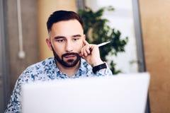 Kaukaski skoncentrowany biznesmen pracuje na laptopie w jego biurze zdjęcia stock