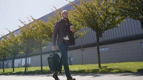 Kaukaski urzędnik trzyma torby pić kawowy w ranku przed pracą blisko biura w kostiumu z szalikiem zdjęcie wideo