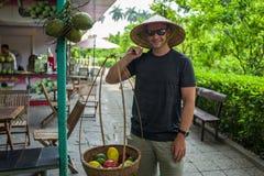 Kaukaskie mężczyzna pozy jako ulicznego rynku sprzedawca w Hanoi, Wietnam Zdjęcia Stock