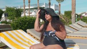Kaukaskie starsze żeńskie starsze osoby w czarnym kapeluszu sunbathes w słońcu podczas gdy siedzący na słońca lounger Przeciw t?u zbiory wideo