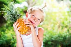 Kaukaskiego chłopiec chwyta Soczysty ananas Wręcza lato Zdjęcia Royalty Free
