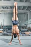 Kaukaskiego mężczyzna akrobacj równowagi gimnastyczna postura przy gym tłem Obraz Stock