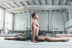 Kaukaskiego mężczyzna akrobacj równowagi gimnastyczna postura przy gym tłem Obraz Royalty Free