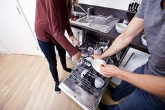 Kaukaskiej pary ładowniczy zmywarka do naczyń w kuchni wpólnie obraz royalty free