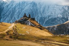Kaukasus berg, Gergeti Treenighetkyrka, Georgia arkivfoto