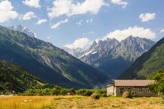 Kaukasus berg och det gamla huset i svanetibyn Mestia landar Arkivbild