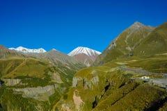 Kaukaz góry w lecie, zielonych wzgórzach, niebieskim niebie i śnieżnym szczycie, Mkinvari droga od Gudauri Stepantsminda Zdjęcia Stock