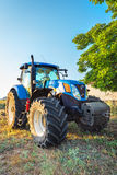 Kavarna, Bulgaria - July 10, 2015: New Holland T7.250 Tractor. And blue agricultural trailer on stubble field Stock Image