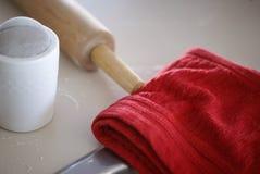 Kavel, ströare för vit blomma och en använd röd handduk, när göra julkakor arkivbild